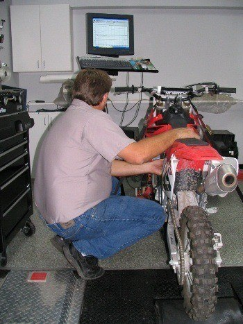 Employee performing service on a motorcycle.